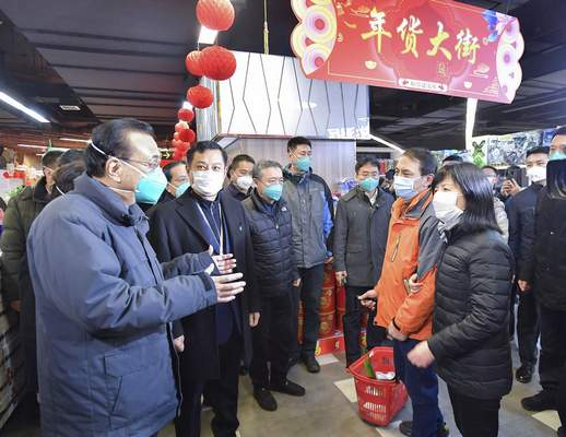 In this photo released by China's Xinhua News Agency, Chinese Premier Li Keqiang, left, speaks with people at a supermarket in Wuhan in central China's Hubei province, Monday, Jan. 27, 2020. (Li Tao/Xinhua via AP)