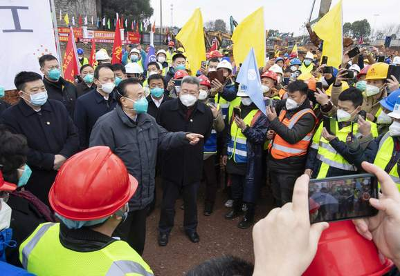 In this photo released by China's Xinhua News Agency, Chinese Premier Li Keqiang, fourth left, speaks with construction workers at the site of makeshit field hospital being built in Wuhan in central China's Hubei province, Monday, Jan. 27, 2020.  (Li Tao/Xinhua via AP)