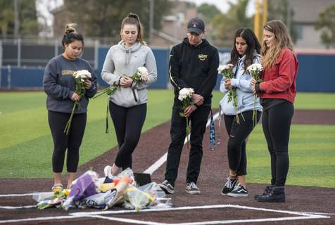 Helicopter Crash-Kobe Bryant Killed Orange Coast College students and friends of baseball coach John Altobelli lay flowers at home plate at the Orange Coast College baseball field in Costa Mesa on Sunday, Jan. 26, 2020. Coach Altobelli, his wife Keri and daughter Alyssa were killed in the helicopter crash that also killed former Lakers star Kobe Bryant. (Leonard Ortiz/The Orange County Register via AP) (Leonard Ortiz