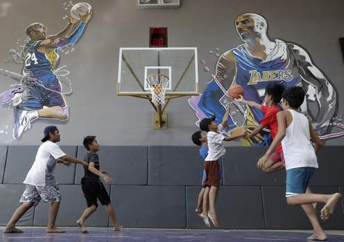 APTOPIX Philippines Obit Bryant Boys plays beside images of former NBA basketball player Kobe Bryant at the