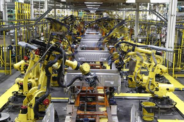 FILE - In this Sept. 27, 2018, file photo robots weld the bed of a 2018 Ford F-150 truck on the assembly line at the Ford Rouge assembly plant in Dearborn, Mich. (AP Photo/Carlos Osorio, File)