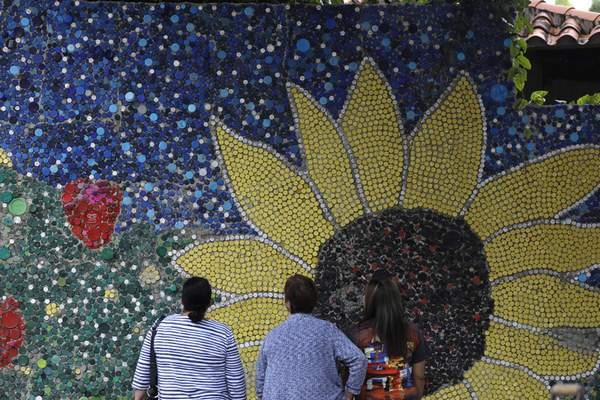 Associated Press People look at a mosaic on the outskirts of Caracas, Venezuela, made by artist Oscar Olivares in El Hatillo out of thousands of plastic bottle caps.
