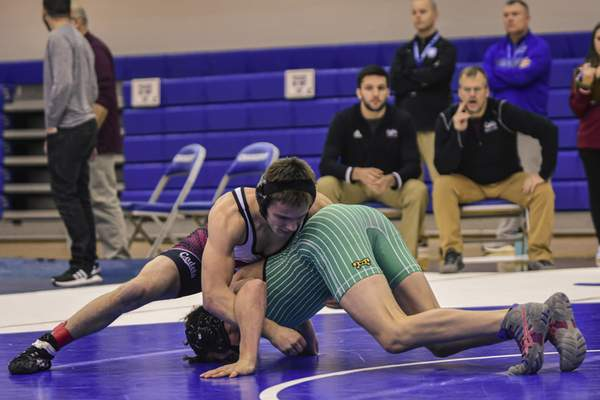 Mike Moore | The Journal Gazette Concordia Lutheran's Matt Goeglein, left and Eastside's Kristopher Patrick compete during the IHSAA Wrestling Sectional at Carroll High School on Saturday.