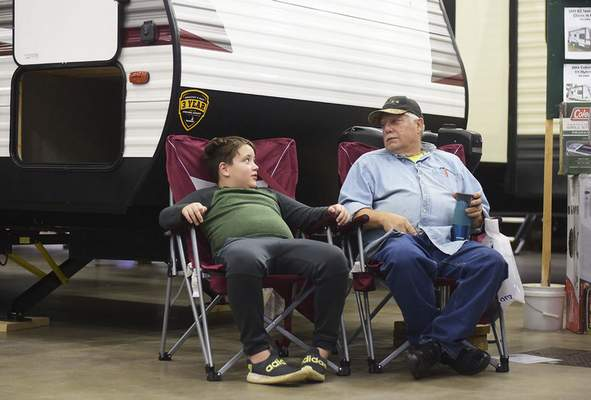 Katie Fyfe   The Journal Gazette  Sawyer McEvoy, 8, sits with his grandfather Leo Heimann outside of an RV during the Fort Wayne RV & Camping Show at the Allen County War Memorial Coliseum on Saturday.