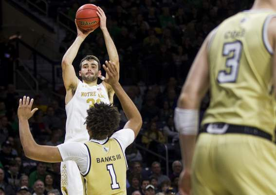 Notre Dame's John Mooney, top, shoots a 3-pointer over Georgia Tech's James Banks III (1) during the second half of an NCAA college basketball game Saturday, Feb. 1, 2020, in South Bend, Ind. Notre Dame won 72-80. (AP Photo/Robert Franklin)