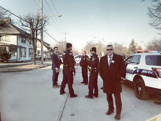 Jamie Duffy | The Journal Gazette Sgt. Tim Hughes, foreground, stands with other Fort Wayne Police Department officers at the scene of a non-fatal shooting on South Wayne Street in January. Hughes leads the department's homicide unit.