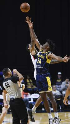 Mike Moore | The Journal Gazette Mad Ants forward Alize Johnson and Raptors forward Devin Robinson at the tipoff to start the first quarter at Memorial Coliseum on Monday.
