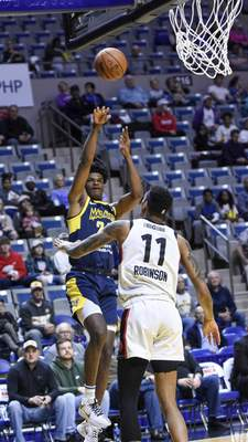 Mike Moore | The Journal Gazette Mad Ants forward Alize Johnson puts up a shot over Raptors forward Devin Robinson in the first quarter at Memorial Coliseum on Monday.