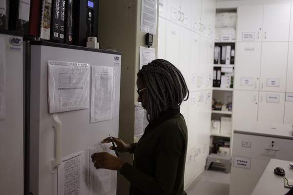 FILE - In a Nov. 30, 2016 file photo, pharmacist Mary Chindanyika looks at documents on a fridge containing a trial vaccine against HIV on the outskirts of Cape Town, South Africa. (AP Photo/Schalk van Zuydam, File)