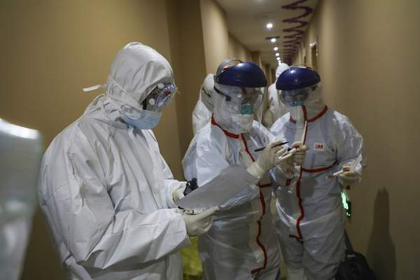 A medical worker in a protective suit writes on a tube after collecting a sample for nucleic acid tests from a suspected virus patient at a hotel being used to place people in medical isolation in Wuhan in central China's Hubei Province, Tuesday, Feb. 4, 2020. (Chinatopix via AP)