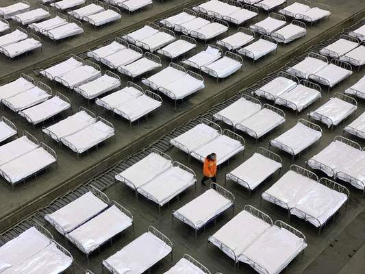 Workers arrange beds in a convention center that has been converted into a temporary hospital in Wuhan in central China's Hubei Province, Tuesday, Feb. 4, 2020. (Chinatopix via AP)