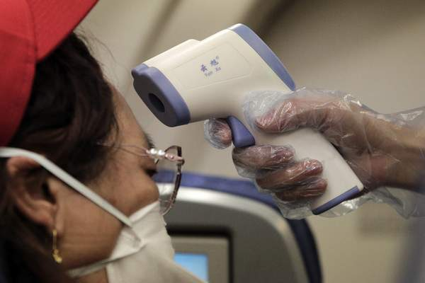A stewardess takes the temperature of passenger as a preventive measure for the coronavirus on an Air China flight from Melbourne to Beijing before it land at Beijing Capital International Airport in China, Tuesday, Feb. 4, 2020. (AP Photo/Andy Wong)