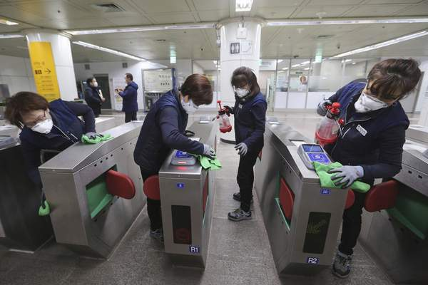 FILE - In this Jan. 28, 2020, file photo, employees disinfect ticket gates in hopes to prevent the contraction of the coronavirus at a subway station in Seoul, South Korea. (AP Photo/Ahn Young-joon, File)