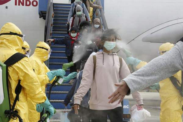 FILE - In this Sunday, Feb. 2, 2020, file photo released by the Indonesian Foreign Ministry, Indonesians who arrived from Wuhan, China, are sprayed with antiseptic at Hang Nadim Airport in Batam, Indonesia. (Indonesian Foreign Ministry via AP)