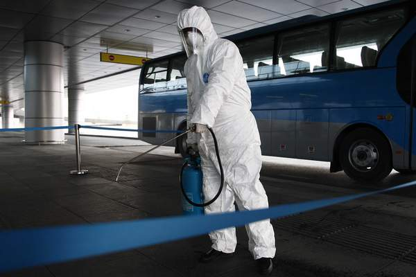 FILE - In this Feb. 1, 2020, file photo, State Commission of Quality Management staff in protective gear disinfects a ground transportation area at the Pyongyang Airport in Pyongyang, North Korea. (AP Photo/Jon Chol Jin, File)