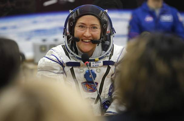 FILE - In this Thursday, March 14, 2019 file photo, U.S. astronaut Christina Koch, member of the main crew of the expedition to the International Space Station (ISS), speaks with her relatives through a safety glass prior the launch of Soyuz MS-12 space ship at the Russian leased Baikonur cosmodrome, Kazakhstan. (AP Photo/Dmitri Lovetsky, Pool)
