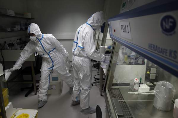 Associated Press Lab scientists in hazmat gear manipulate potentially infected patient samples Thursday at the Pasteur Institute in Paris.
