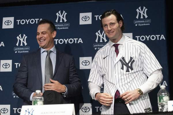 FILE - In this Dec. 18, 2019, file photo, New York Yankees manager Aaron Boone, left, smiles as Gerrit Cole tries on a Yankee jersey as he is introduced in New York. The pitcher agreed to a 9-year $324 million contract.