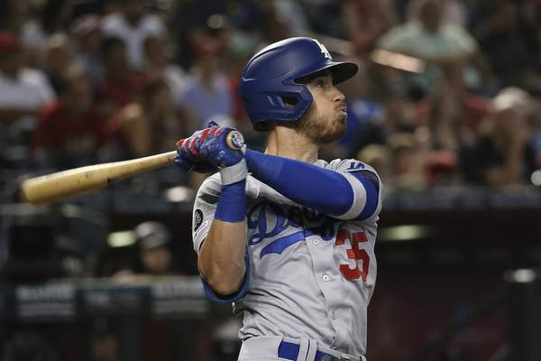 FILE - In this Sept. 1, 2019, file photo, Los Angeles Dodgers' Cody Bellinger watches the flight of his home run against the Arizona Diamondbacks during the ninth inning of a baseball game in Phoenix. In what's become a familiar refrain, the Dodgers arrive at camp still looking for their first World Series championship since 1988. After losing in two straight World Series, they were ousted by Washington in five games in the NL Division Series last fall. (AP Photo/Ross D. Franklin, File)