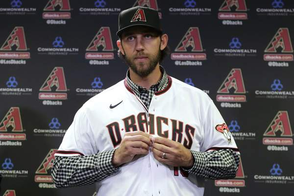 FILE - In this Dec. 17, 2019, file photo, newly acquired Arizona Diamondbacks pitcher Madison Bumgarner puts on a jersey after being introduced during a team availability in Phoenix. The Diamondbacks added a handful of veteran free agents during the offseason, including Bumgarner, outfielder Kole Calhoun, catcher Stephen Vogt and reliever Héctor Rondón. The left-handed Bumgarner â€