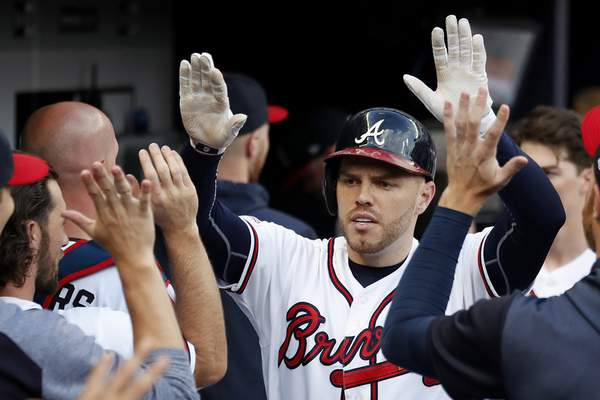 FILE - In this June 19, 2019, file photo, Atlanta Braves first baseman Freddie Freeman (5) celebrates in the dugout after hitting a two-run home run in the first inning of a baseball game against the New York Mets in Atlanta. Two straight NL East titles have led to first-round playoff exits for Atlanta, and the Braves' frustration only grew as they watched division rival Washington win the World Series. Now Freddie Freeman says