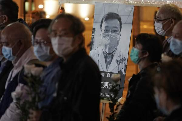 Associated Press In Hong Kong, people attend a vigil Friday for Li Wenliang, a doctor who died from China's new virus after being reprimanded for warning about it.