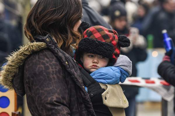 Mike Moore | The Journal Gazette Hanging around with his mother Sarah Leitch on Saturday, Ian Leith, 1 stays bundled up while watching family members play a game of cornhole during the 5th annual Weather the Fort celebration on The Landing downtown.