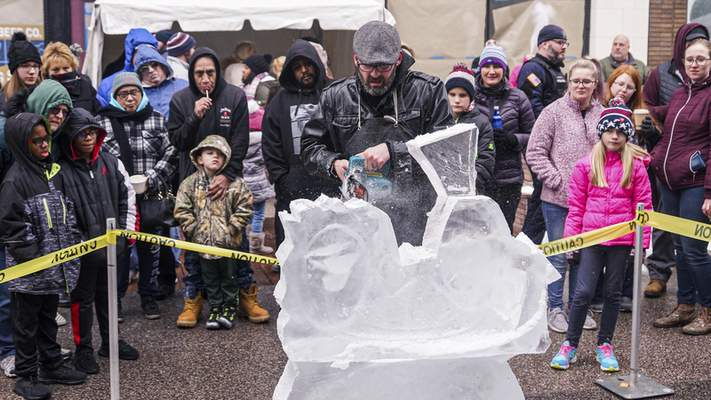 Mike Moore | The Journal Gazette Spectators huddle around Nate Johnson on Saturday to watch him sculpt an ice sculpture on The Landing for the 5th annual Weather the Fort celebration.