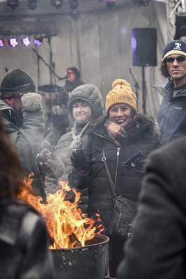 Mike Moore | The Journal Gazette Guests attending the Weather the Fort winter celebration on Saturday huddle around burn barrels for warmth while having a laugh and listening to live music on The Landing downtown.
