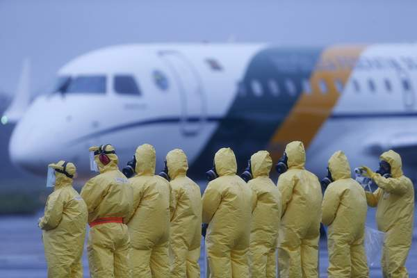 Soldiers wear protective suits during the arrival of Brazilians repatriated from Wuhan, China, the epicenter of the coronavirus, at the Annapolis Air Force Base, in Anapolis city, Goias state, Brazil, Sunday, Feb. 9, 2020. (AP Photo/Beto Barata)