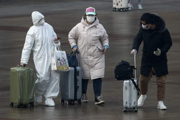 A passenger wearing a full-body protective suit catches the eyes of others as they walk out from the Beijing railway station in Beijing, Tuesday, Feb. 11, 2020. (AP Photo/Andy Wong)