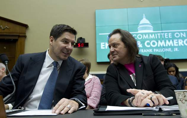 FILE - In this Feb. 13, 2019, file photo Sprint Corporation Executive Chairman Marcelo Claure, left, speaks with T-Mobile US CEO and President John Legere during the House Commerce subcommittee hearing on Capitol Hill in Washington. (AP Photo/Jose Luis Magana, File)