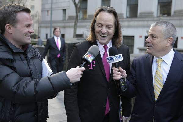 FILE - In this Jan. 15, 2020, file photo T-Mobile chief executive John Legere speaks to reporters as he leaves the courthouse in New York. (AP Photo/Seth Wenig, File)