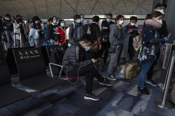 Masked passengers line up to board a flight for Beijing at the airport in Hong Kong on Sunday, Feb. 9, 2020. (AP Photo/Ng Han Guan)