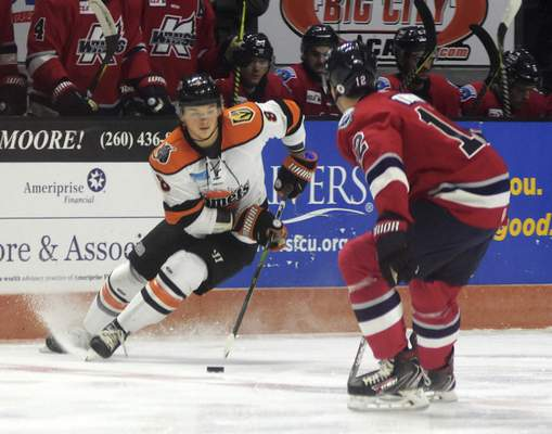 Katie Fyfe | The Journal Gazette  Komets forward Drake Rymsha carries the puck while Kalamazoo defenseman Aaron Thow tries to stop him during the first period at Memorial Coliseum on Wednesday.