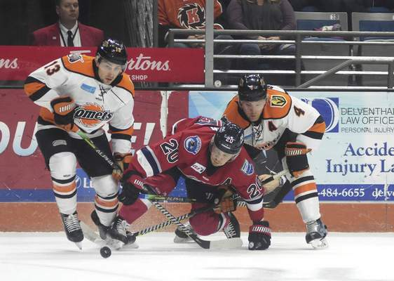 Katie Fyfe | The Journal Gazette The Komets' Anthony Petruzzelli, left, and Jason Binkley battle Kalamazoo's Boston Leier for the puck during Wednesday's game at Memorial Coliseum.