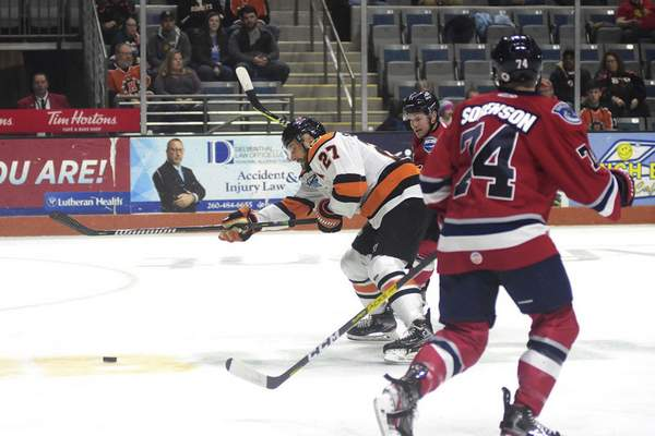 Katie Fyfe | The Journal Gazette  Komets forward Shawn Szydlowski chases after the puck during the first period against Kalamazoo Wings at Memorial Coliseum on Wednesday.