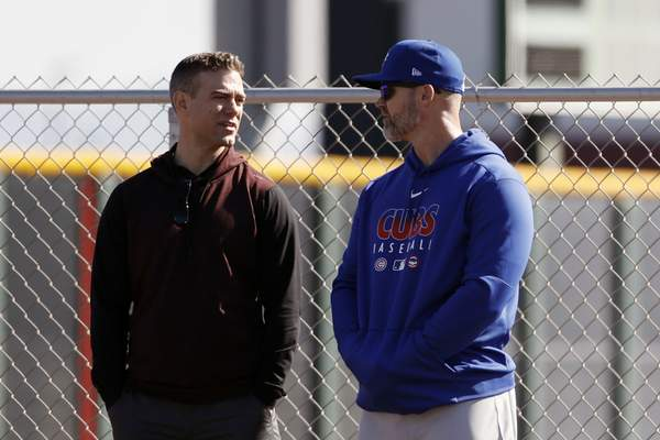 Chicago Cubs president of baseball operations Theo Epstein, left, talks with manager David Ross during a spring training baseball workout Wednesday, Feb. 12, 2020, in Mesa, Ariz. (AP Photo/Gregory Bull)