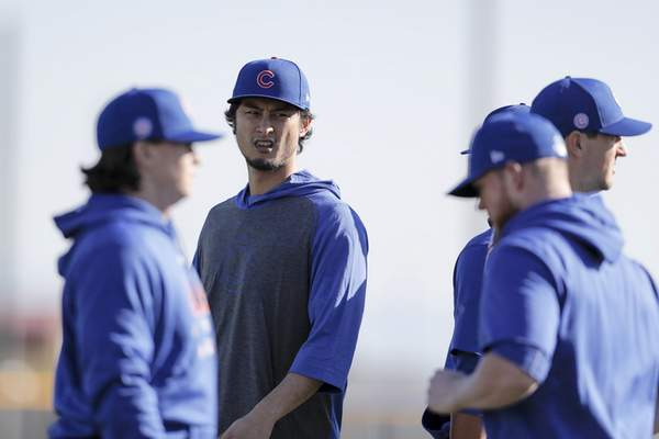 Chicago Cubs pitcher Yu Darvish, second from left, talks with other pitchers during a spring training baseball workout Wednesday, Feb. 12, 2020, in Mesa, Ariz. (AP Photo/Gregory Bull)