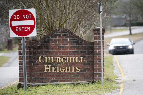 A police officer blocks a road near an entrance to the Churchill Heights neighborhood Thursday, Feb. 13, 2020, in Cayce, S.C., where 6-year-old Faye Marie Swetlik recently went missing just after getting off a school bus. (AP Photo/Sean Rayford)