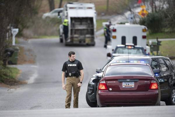 A Cayce police officer approaches a vehicle at a road block near an entrance to the Churchill Heights neighborhood Thursday, Feb. 13, 2020, in Cayce, S.C., where six year-old Faye Marie Swetlik recently went missing. (AP Photo/Sean Rayford)