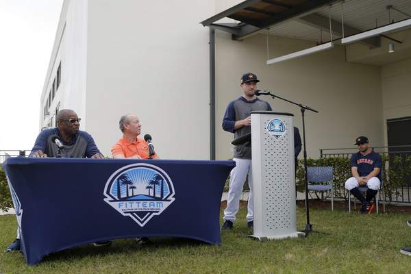 Houston Astros' Alex Bregman delivers a statement from the podium as teammate Jose Altuve, seated at right, listens along with manager Dusty Baker, left, and owner Jim Crane, second from left, during a news conference before the start of the first official spring training baseball practice for the team Thursday, Feb. 13, 2020, in West Palm Beach, Fla. (AP Photo/Jeff Roberson) ;
