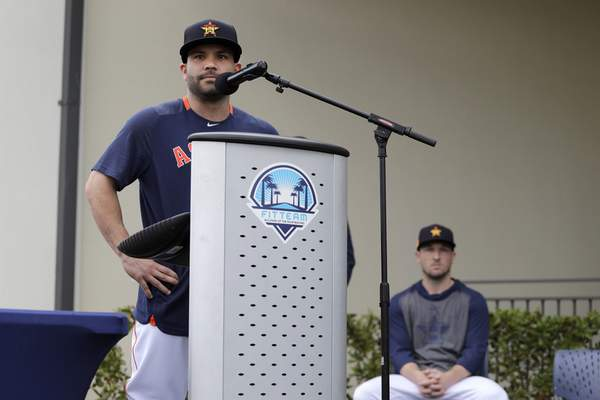 Houston Astros' Jose Altuve speaks at a podium as teammate Alex Bregman, seated right, looks on during a news conference before the start of the first official spring training baseball practice for the team Thursday, Feb. 13, 2020, in West Palm Beach, Fla. (AP Photo/Jeff Roberson)