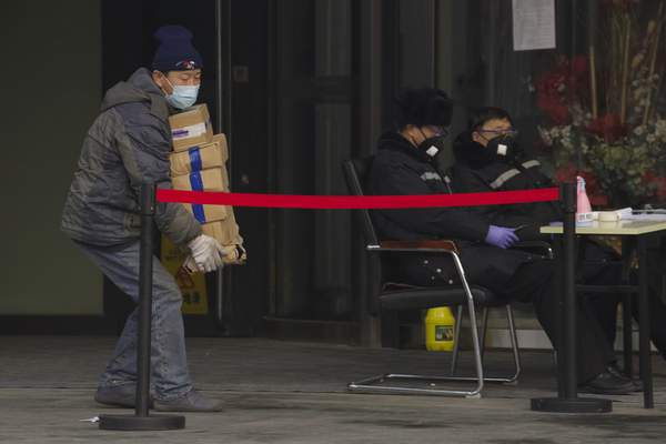 A delivery man carries goods near a health checkpoint into a office building in Beijing, China Thursday, Feb. 13, 2020. (AP Photo/Ng Han Guan)