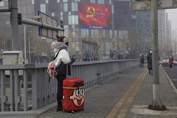 A traveler stands on a bridge near a display showing government propaganda in the fight against the COVID-19 viral illness in Beijing, China Thursday, Feb. 13, 2020. (AP Photo/Ng Han Guan)
