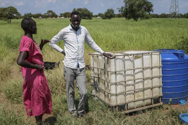 In this photo taken Monday, Oct. 1, 2018, residents stand next to a white container previously used for hazardous chemicals that was then used for several years to hold drinking water before the oil company put a stop to the practice, on the road between Melut and Paloch town, in South Sudan. (AP Photo/Sam Mednick)