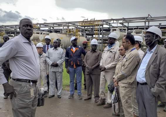In this photo taken Monday, Aug. 26, 2019, officials from the Chinese-led Dar Petroleum Operating Company and the Ministry of Petroleum, including Minister of Petroleum and Mining Awow Daniel Chuang, center wearing blue jeans, gather during a trip to the oil fields in Paloch, South Sudan. (AP Photo)