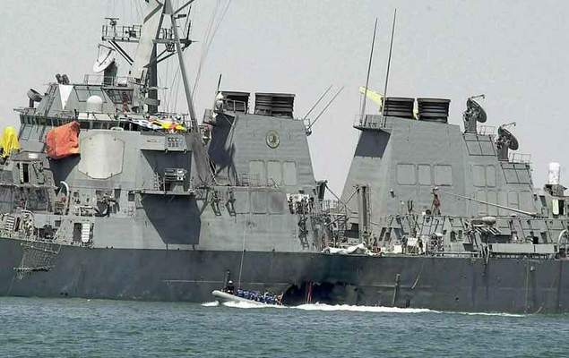 FILE - In this Oct. 15, 2000 file photo, experts in a speed boat examine the damaged hull of the USS Cole at the Yemeni port of Aden after an al-Qaida attack that killed 17 sailors. (AP Photo/Dimitri Messinis, File)