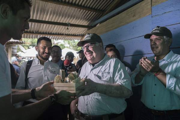 In this Jan. 29, 2020 photo, Howard Buffett receives presents during a visit, with Colombia's President Ivan Duque, right, to a cocoa farm in La Gabarra, Colombia. (AP Photo/Ivan Valencia)