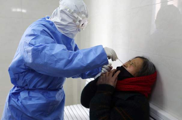 A doctor takes a swab from a woman to test for the COVID-19 virus at a fever clinic in Yinan county in eastern China's Shandong province on Wednesday, Feb. 12, 2020. (Chinatopix Via AP)